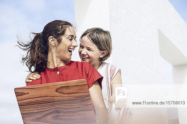 Mädchen beobachtet Mutter mit Laptop mit Holzabdeckung