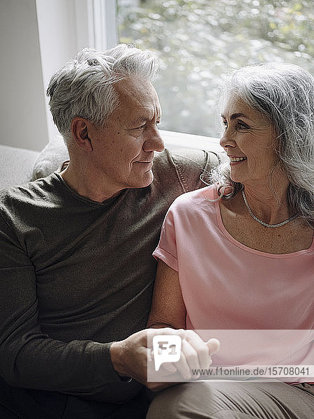 Affectionate senior couple relaxing on couch at home