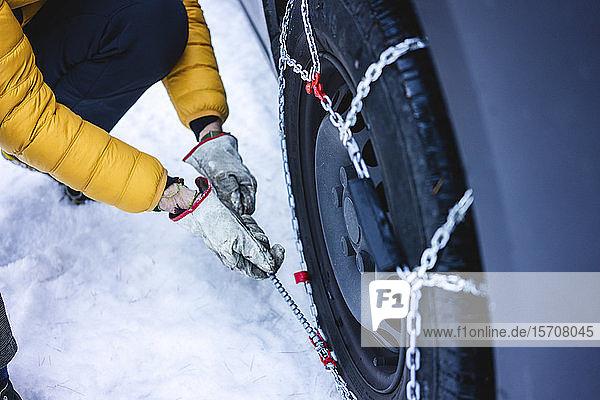 Mann legt die Schneeketten an sein Auto