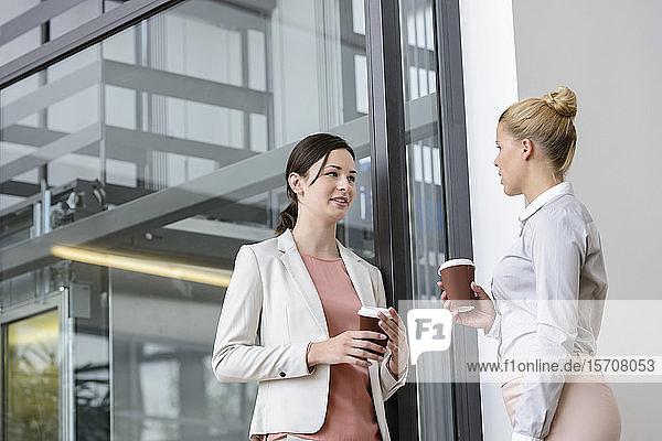 Two businesswomen having coffee break outside office building