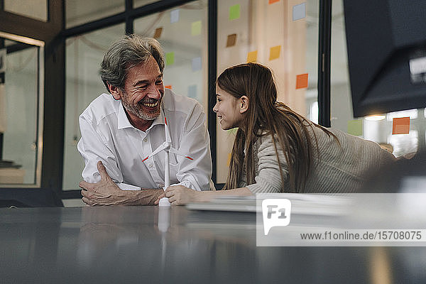 Happy senior buisinessman and girl with wind turbine model in office