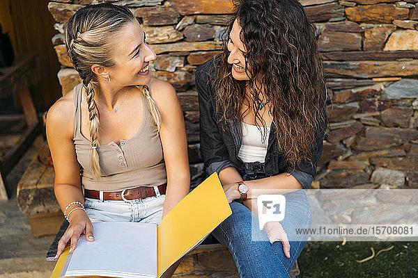 Zwei glückliche Frauen mit einer Mappe sitzen an einem Steinhaus