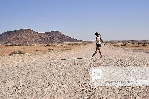 Frau  die mitten auf einem Feldweg geht  Damaraland  Namibia