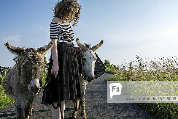Young woman on country road with donkeys carrying baggage