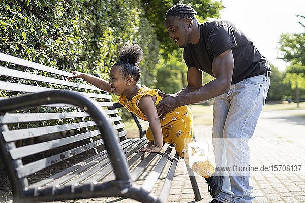Vater hilft Tochter beim Klettern auf eine Parkbank
