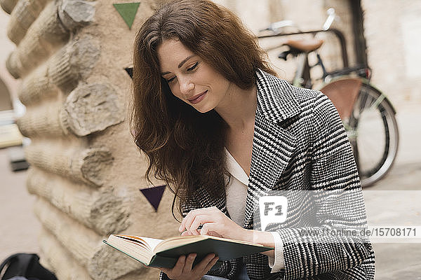 Young woman reading a book outdoors in the city