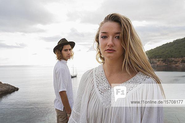Porträt einer jungen Frau vor dem Meer mit ihrem Freund im Hintergrund  Ibiza  Balearen  Spanien