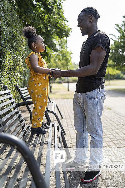 Vater mit Tochter auf einer Parkbank stehend Vater mit Tochter auf einer Parkbank stehend