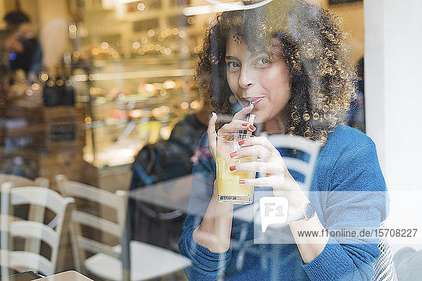 Portrait of woman drinking a smoothie behind windowpane in a cafe