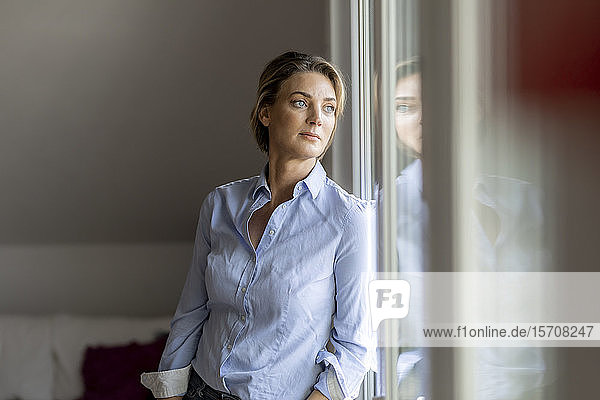 Mature woman looking out of the window at home