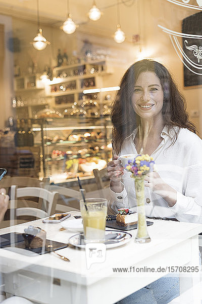 Portrait of smiling young woman behind windowpane in a cafe