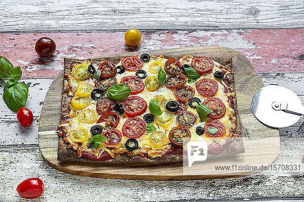 Low carb flax seed pizza with cheese  cherry tomatoes  olives and basil