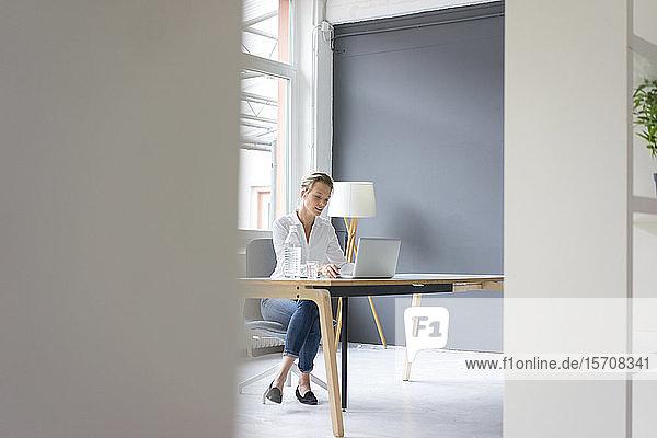Junge Geschäftsfrau mit Laptop am Schreibtisch im Büro