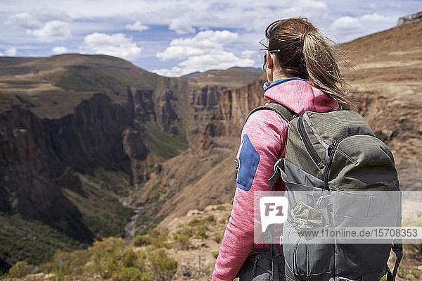 Frau steht auf einem Hügel an den Maletsunyane-Fällen und genießt die Aussicht  Lesotho