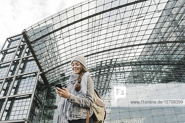 Happy young woman using smartphone at the central station,  Berlin,  Germany