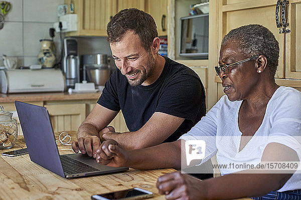 Senior woman and smiling man sitting at kitchen table sharing laptop