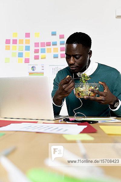 Mann mit Laptop sitzt am Schreibtisch im Büro und macht Mittagspause