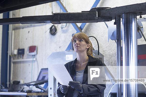 Automechanikerin  die in einer Reparaturwerkstatt auf den Boden eines Autos schaut