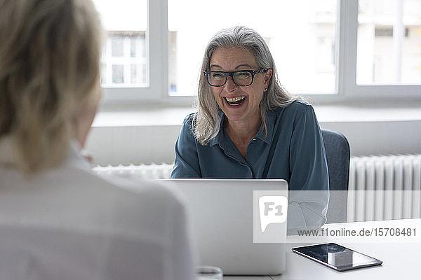 Lachende reife Geschäftsfrau im Gespräch mit junger Geschäftsfrau am Schreibtisch im Büro