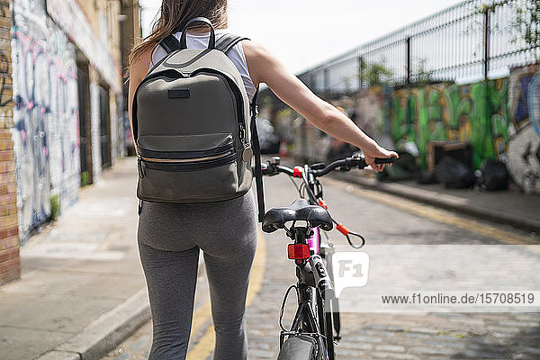 Junge Frau schiebt ihr Fahrrad in der Stadt