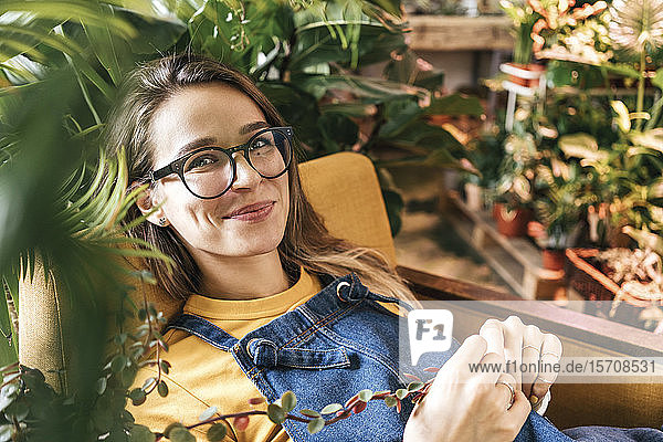 Portrait of a smiling young woman sitting in armchair surrounded by plants