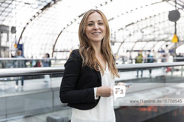 Porträt einer lächelnden Frau mit Smartphone am Bahnhof  Berlin  Deutschland