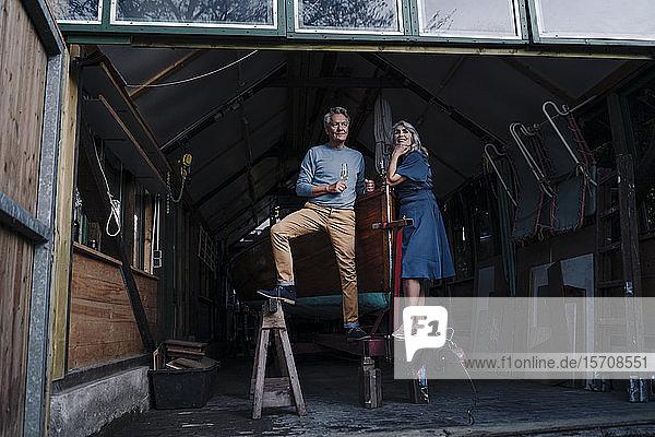 Älteres Ehepaar in einem Bootshaus mit einem Glas Champagner