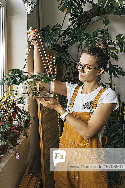 Young woman holding plant in a box with water