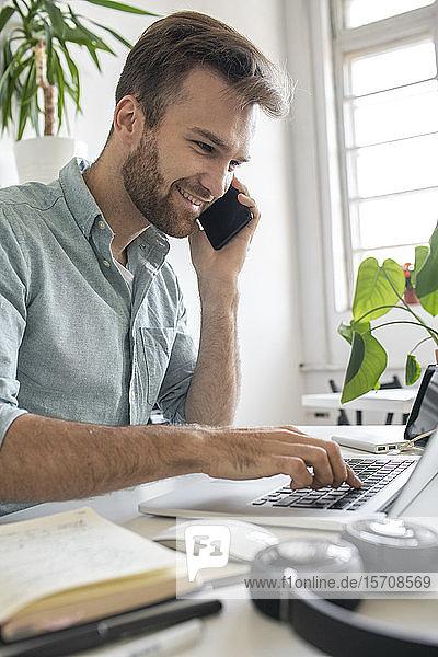 Lächelnder Mann am Telefon am Schreibtisch im Büro