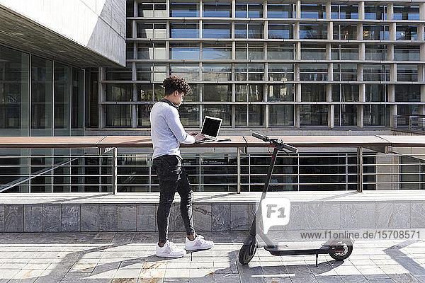 Junger Mann mit E-Scooter mit Laptop in der Stadt