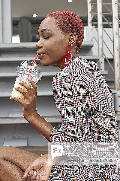 Young woman drinking a cold drink  closed eyes