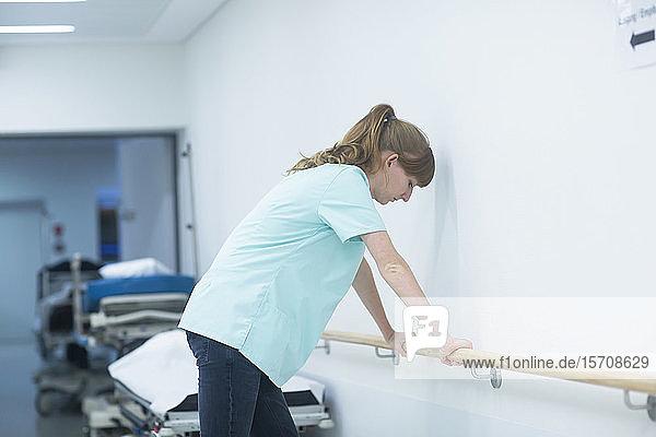 Radiologin  die in einem Krankenhaus auf einem Geländer ruht