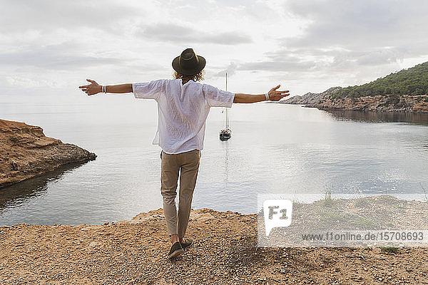 Rückenansicht eines glücklichen jungen Mannes vor dem Meer  Ibiza  Balearen  Spanien