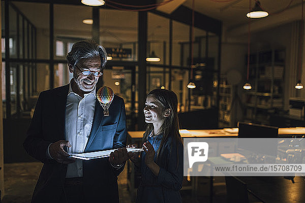 Happy senior buisinessman and girl with hot-air balloon and shining tablet in office