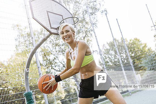 Blonde Frau spielt Basketball