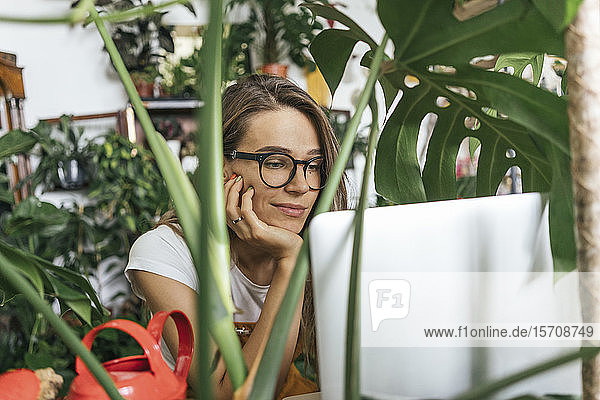 Young woman using laptop surrounded by plants