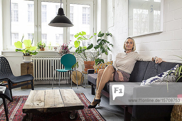 Mature businesswoman sitting on couch in office lounge