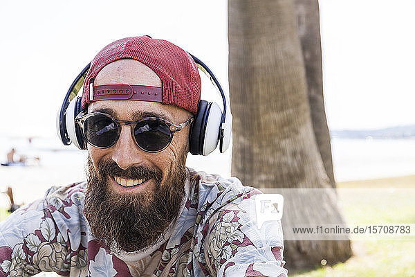 Reifer Mann mit roter Basecap  Sonnenbrille und weißen Kopfhörern Reifer Mann mit roter Basecap, Sonnenbrille und weißen Kopfhörern
