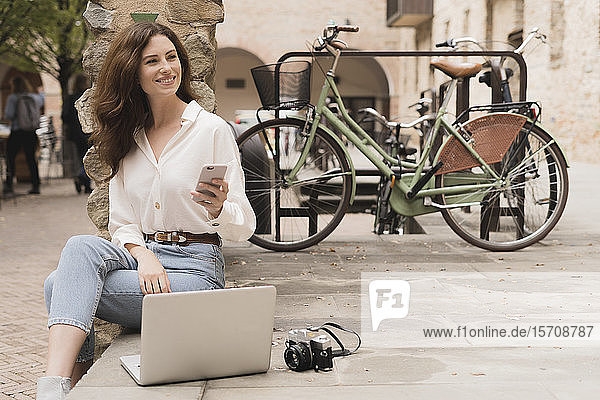 Smiling young woman with smartphone  camera and laptop outdoors