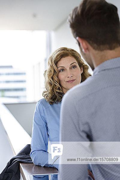 Geschäftsfrau schaut auf amtierenden Geschäftsmann