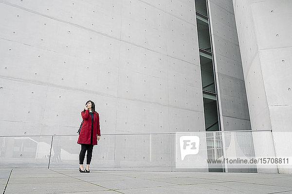 Geschäftsfrau  die in der Nähe eines modernen Gebäudes steht und ein Smartphone benutzt