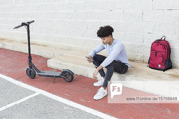 Junger Mann mit E-Scooter und Smartphne im Freien