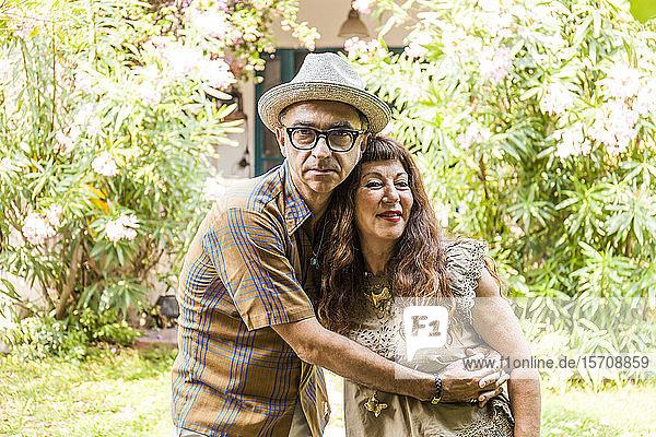 Porträt eines reifen Paares  das sich im Garten umarmt