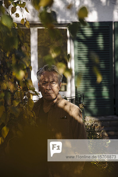 Portrait of a serious senior man at tree in garden