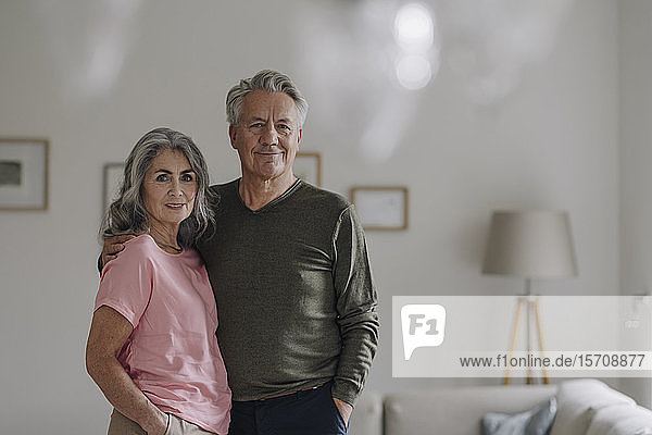 Portrait of confident senior couple standing in living room at home