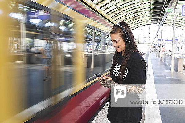 Tätowierte junge Frau mit Kopfhörern am Bahnsteig stehend mit Smartphone  Berlin  Deutschland