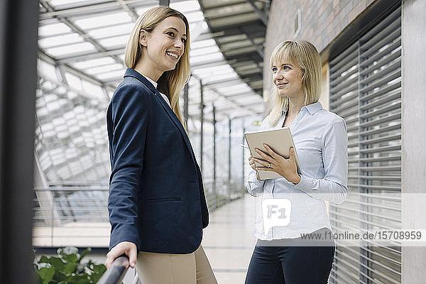 Zwei glückliche junge Geschäftsfrauen mit Tablett in modernem Bürogebäude