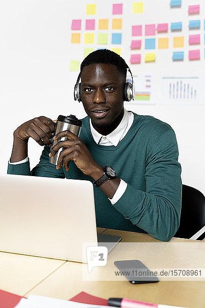 Porträt eines Mannes mit Kaffeetasse und Laptop am Schreibtisch im Büro sitzend