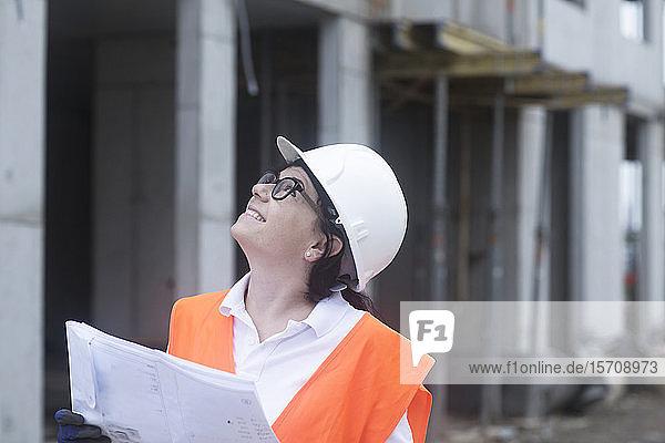 Weibliche Bauingenieurin schaut nach oben  hält Bauplan