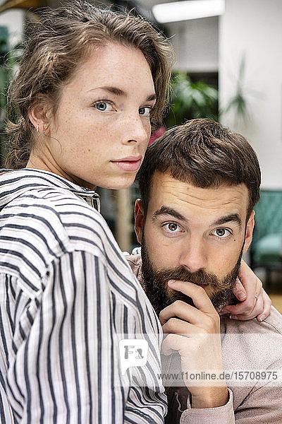Gekoppeltes Paar mit umgebundenen Armen  in die Kamera blickend
